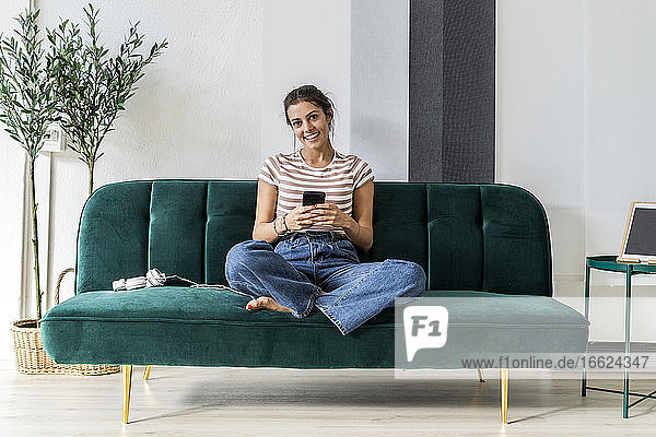 Happy beautiful young businesswoman holding smart phone while sitting on sofa at small office