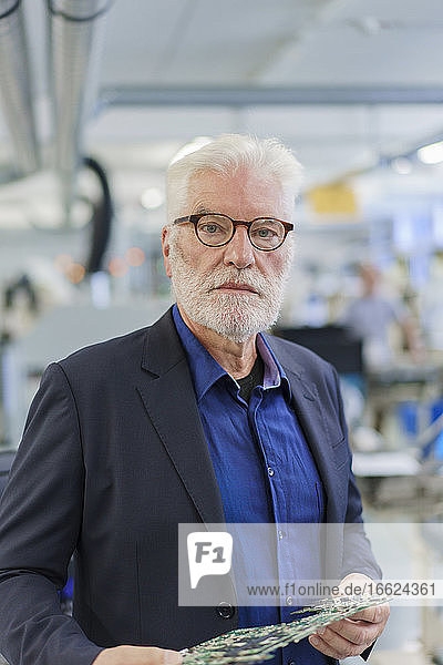 Confident senior male manager holding machine part while standing at factory