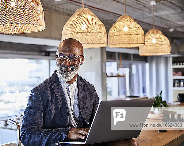 Smiling man looking away while working on laptop sitting at home