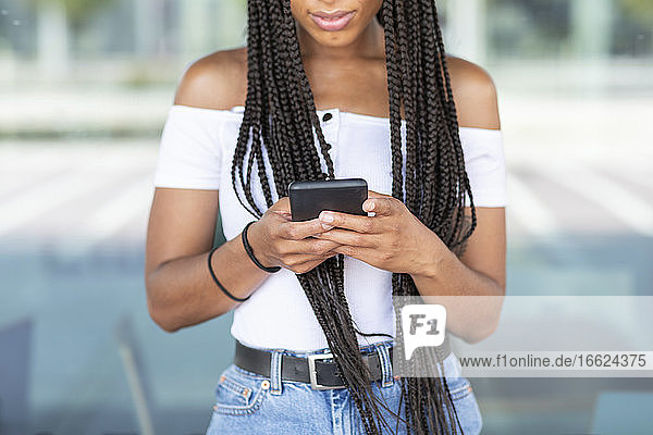 Young woman using mobile phone while standing against glass wall in city