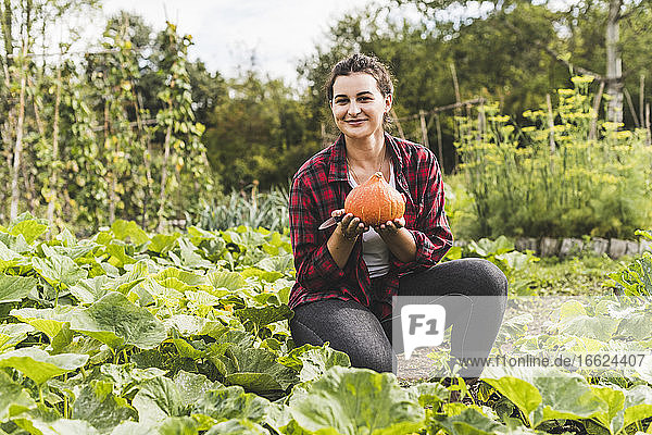 Smiling young woman holding squash while kneeling amidst plants in vegetable garden