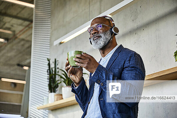 Man listening to music while drinking coffee looking away at home
