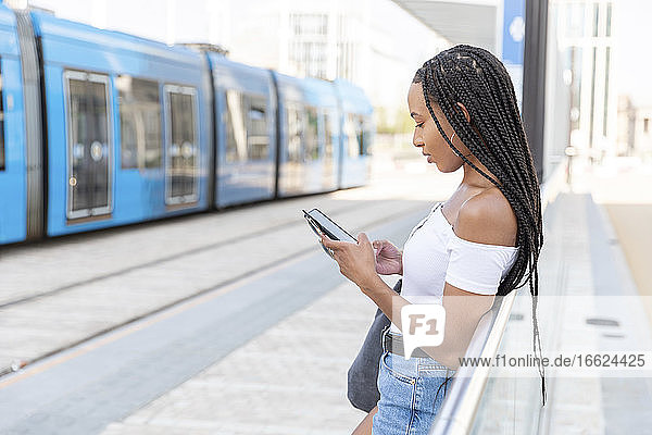 Young woman using phone while standing at railroad station