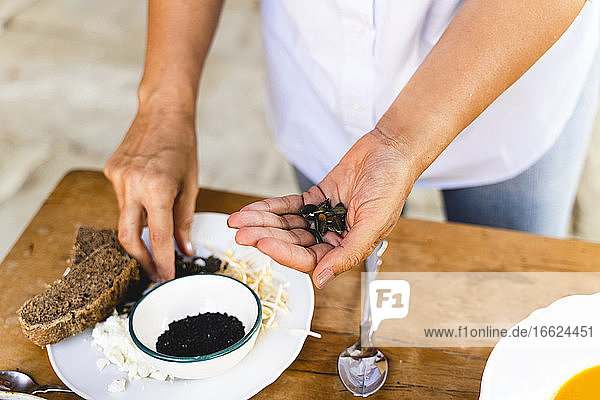 Woman holding black pumpkin seed while standing at table