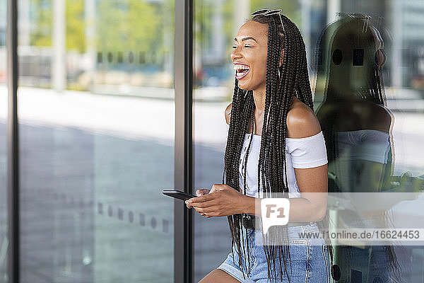 Woman laughing while using mobile phone against glass wall in city