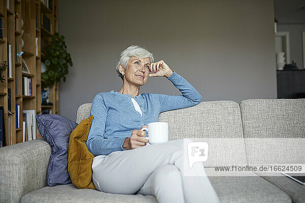 Thoughtful senior woman sitting on sofa holding coffee cup at home