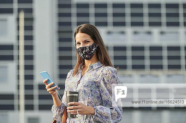 Junge Frau mit Gesichtsmaske  die eine Thermoskanne hält  während sie ein Mobiltelefon in der Stadt benutzt Junge Frau mit Gesichtsmaske, die eine Thermoskanne hält, während sie ein Mobiltelefon in der Stadt benutzt