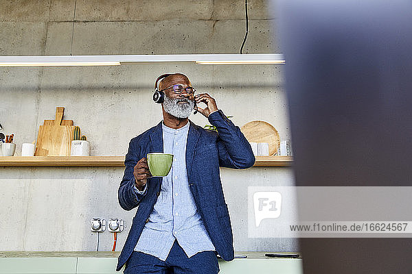 Man with eyes closed listening to music while drinking coffee at home