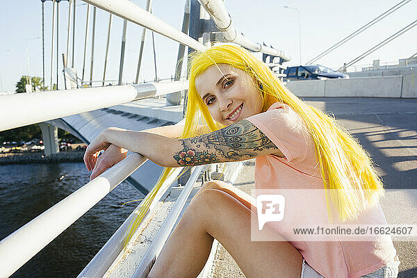 Young woman smiling while sitting on bridge during sunny day