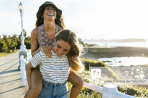 Carefree young woman piggybacking sister on footpath during sunny day