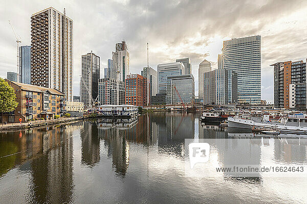 Boats moored at harbor near modern skyscrapers in city against cloudy sky during sunset  London  UK