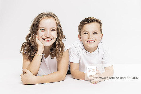 Cute smiling siblings lying on white background