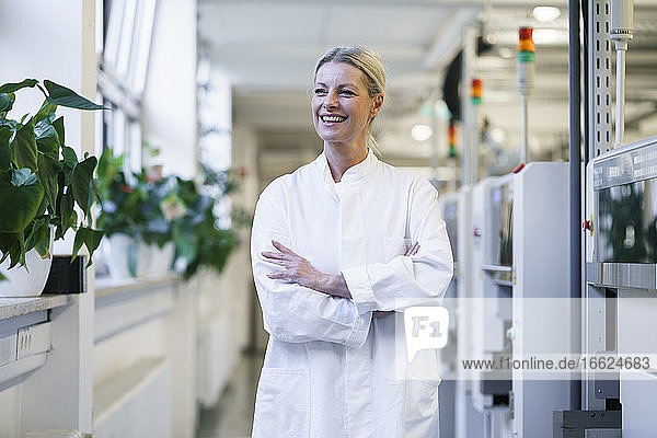 Confident mature female scientist with hands in lab coat pockets standing by machinery at laboratory