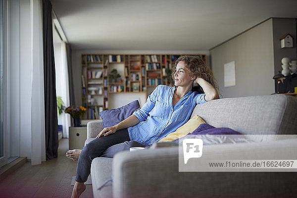 Woman with head in hands resting while sitting on sofa at home