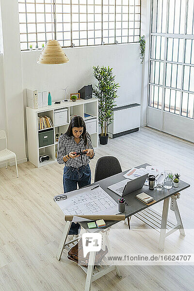 Female design professional photographing floor plan at desk in creative workplace