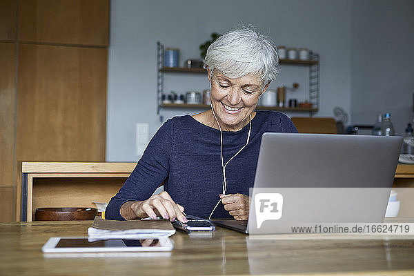 Smiling woman listening to music on smart phone and using laptop while sitting at home