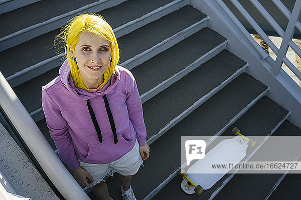 Dyed hair hipster female with skateboard standing on staircase during sunny day
