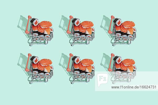 Fresh Japanese sushi nigiri in shopping carts on mint green background