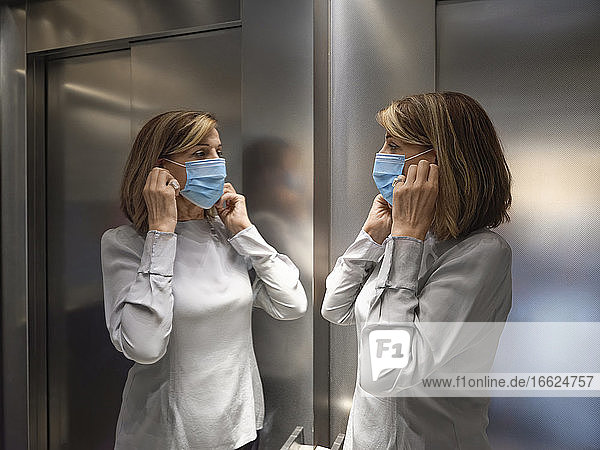 Senior woman wearing protective face mask while standing in elevator during covid-19