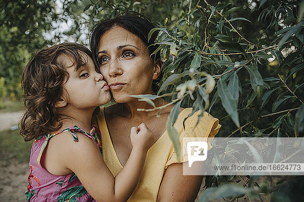 Mother and daughter embracing each other under willow tree
