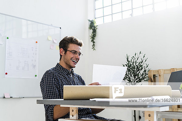 Smiling man working while sitting by desk at office