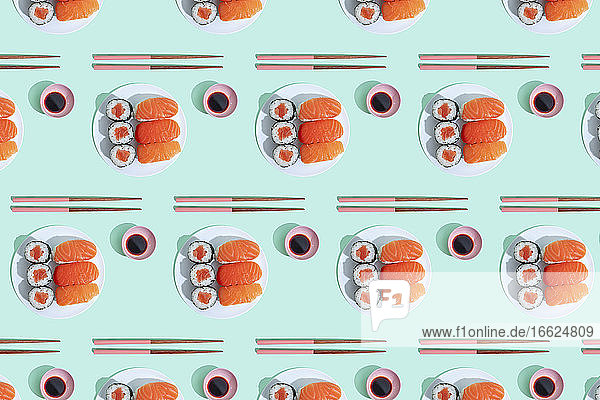 Pattern of plates of sushi against green background