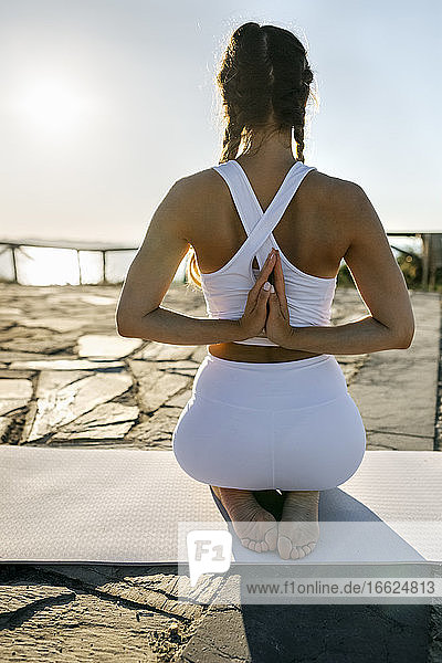 Young woman practicing prayer pose on mat against clear sky at sunset