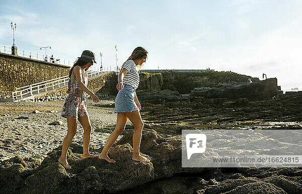 Young women walking on rocks at beach against sky
