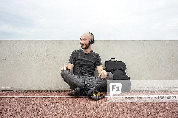 Man wearing inline skates listening music through headphones while sitting on bridge