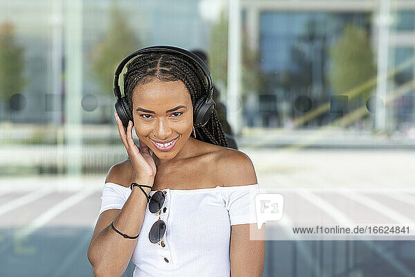 Smiling woman with headphone listening music while standing against glass wall in city