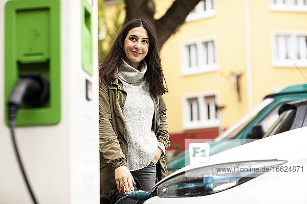 Smiling beautiful woman looking away while standing with hand in pocket and charging electric vehicle at station
