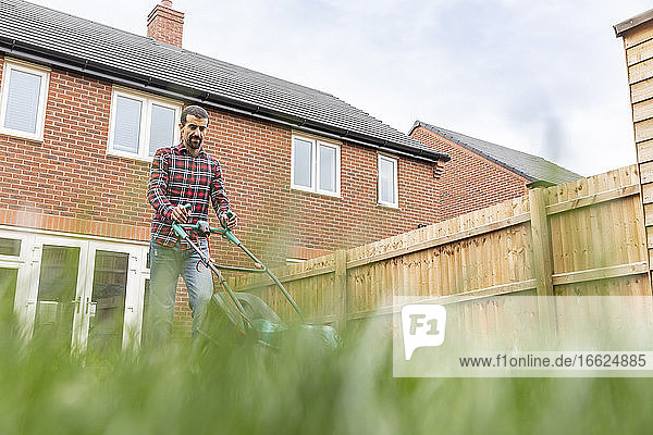 Man mowing lawn with lawn mower at backyard