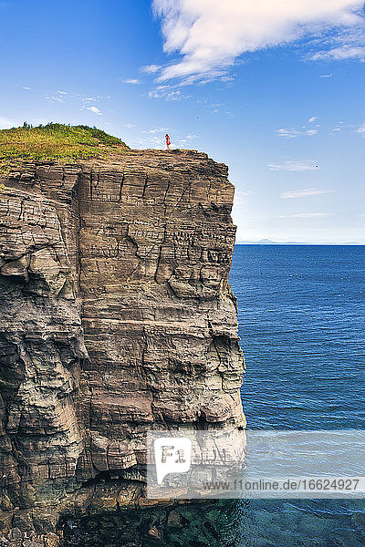 Distant view of woman standing on cliff by sea against sky