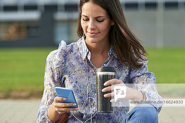 Young woman listening music while using mobile phone in city