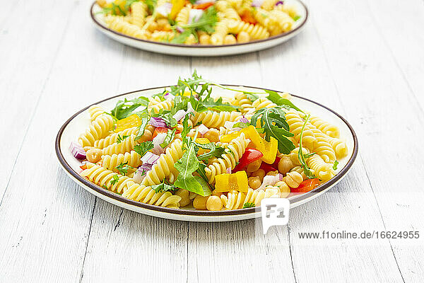 Plate of vegetarian pasta salad with chick-peas  bell pepper  arugula  onion  parsley and basil