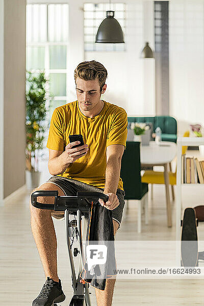 Young man using mobile phone while cycling on exercise equipment at home