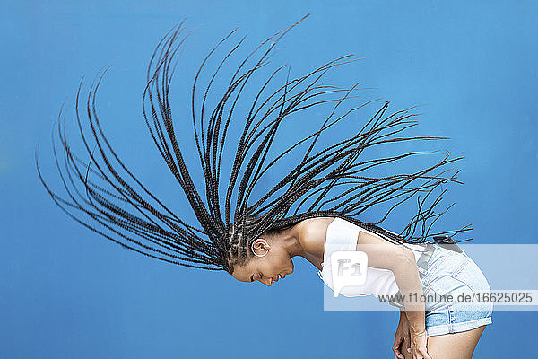 Woman tossing hair against blue wall