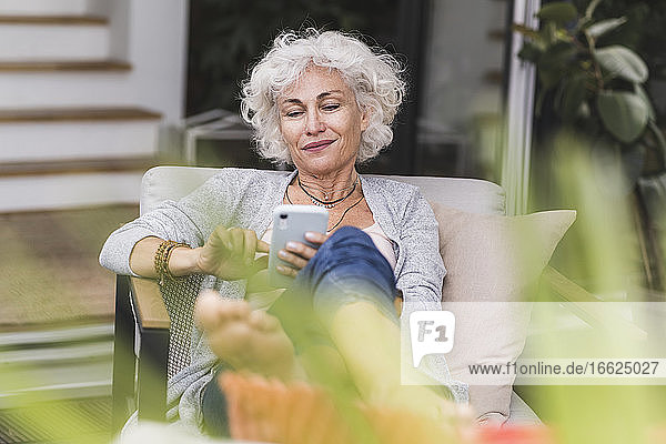 Smiling mature woman texting messaging while sitting on couch at home