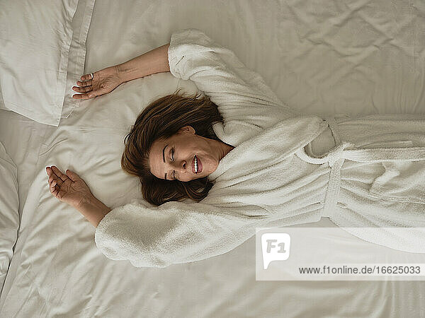 Lächelnde ältere Frau  die auf einem weißen Bett in einem Luxushotelzimmer liegt Lächelnde ältere Frau, die auf einem weißen Bett in einem Luxushotelzimmer liegt