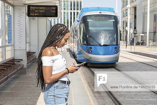 Young woman using phone while standing at tramway