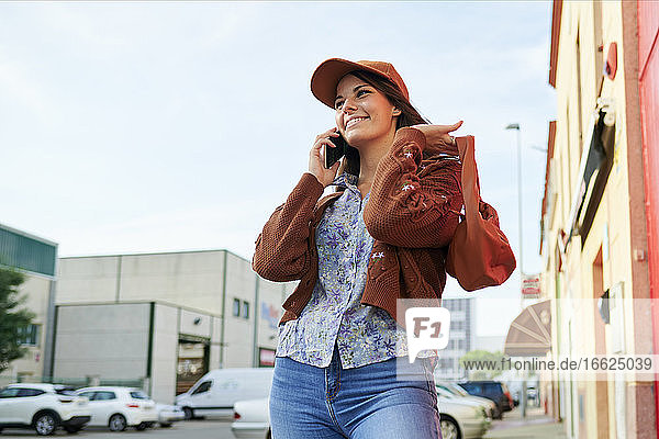 Young woman talking on phone while standing in city
