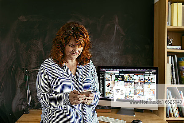Mature woman using phone while standing by desk at home