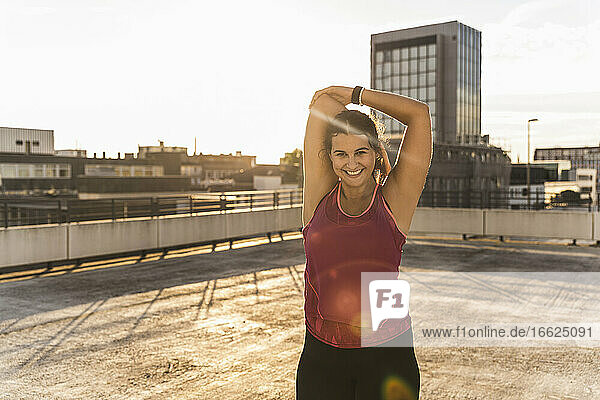 Smiling woman with arms raised exercising on terrace against sky at sunset