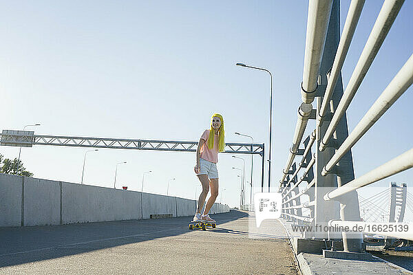 Young woman skateboarding on bridge against clear sky during sunny day