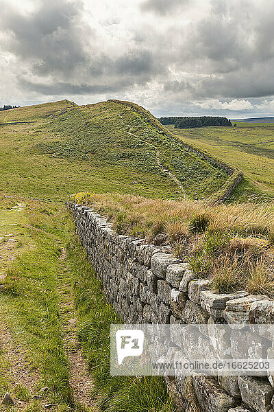 UK  England  Hexham  Clouds over green grassy hills and part of Hadrians Wall