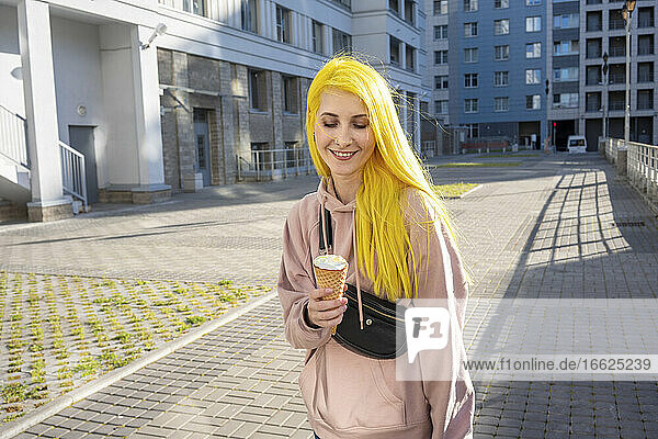 Young woman smiling while looking at ice cream cone standing on street in city during sunny day