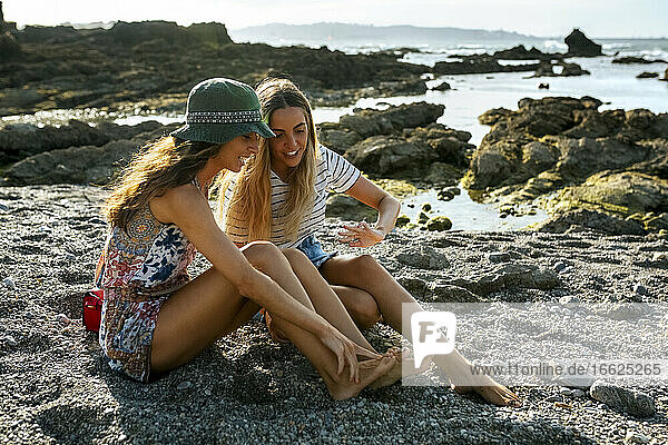 Smiling young woman showing feet to sister while sitting on sand at beach during sunny day