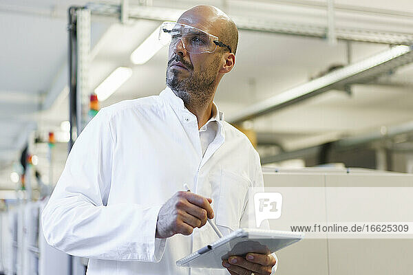 Mature male technician holding digital tablet while looking away at laboratory