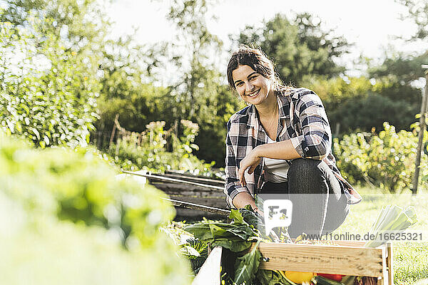 Smiling young woman working while crouching in vegetable garden
