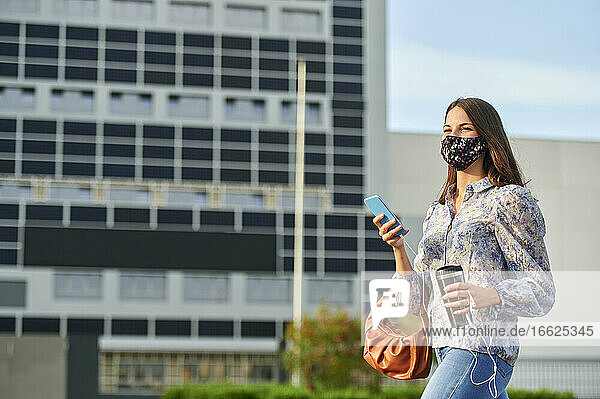 Young woman wearing face mask using mobile phone while walking in city